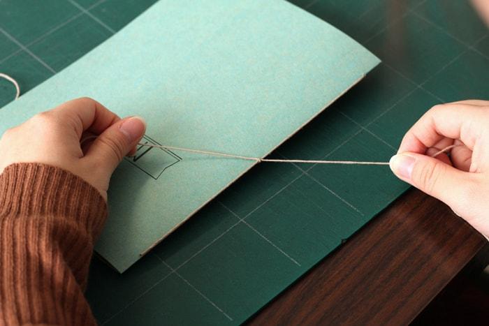 背に沿った糸を固定するように結ぶ