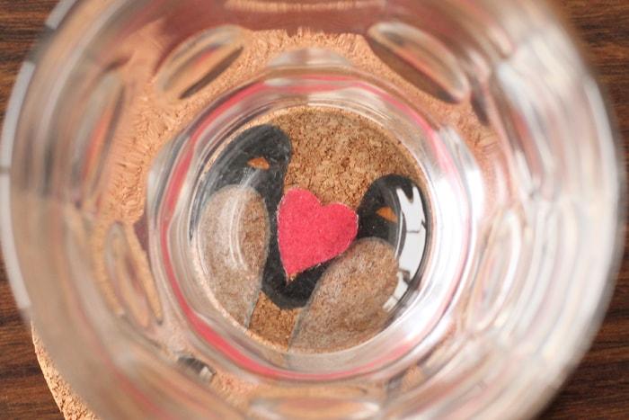 グラスの底にハート模様をデコパージュし、ペンギンの間にハートがあるように見える